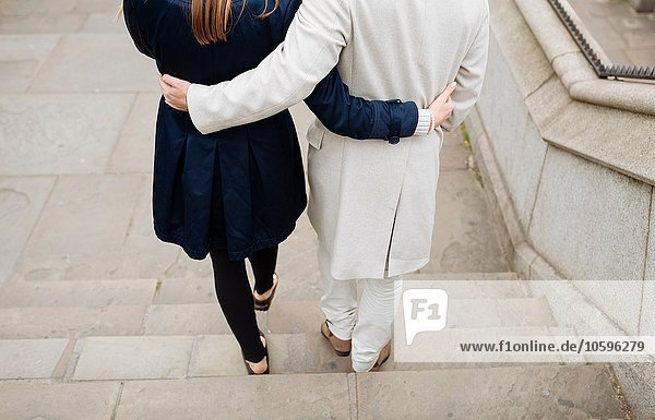Rear view of romantic couple walking down city steps