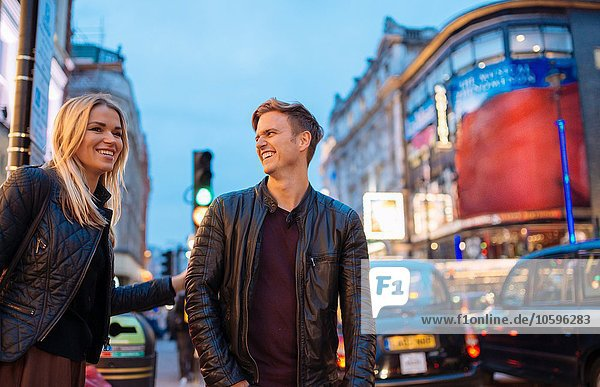 Young couple on city street at night  London  England  UK