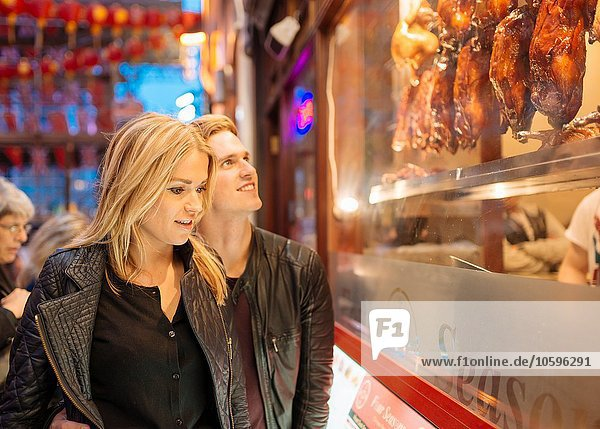 Young couple looking in restaurant window at night  Chinatown  London  England  UK