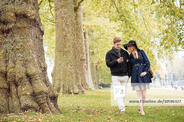 Romantisches junges Paar beim Lesen von Smartphone-Texten im Park  London  England  UK
