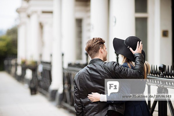 Rear view of romantic young couple strolling on street  London  England  UK