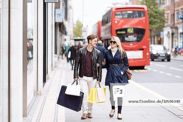 Junges Paar mit Einkaufstüten beim Bummeln  London  England  UK Junges Paar mit Einkaufstüten beim Bummeln, London, England, UK