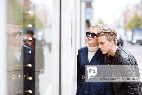 Young couple looking in shop window  London  England  UK
