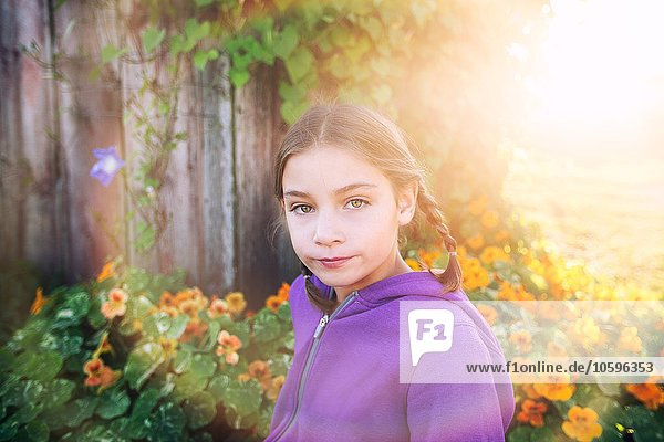 Portrait of girl with plaits in front of orange flowers looking at camera