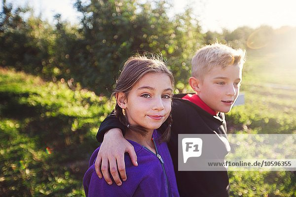 Boy in orchard with arms around girl  looking at camera smiling