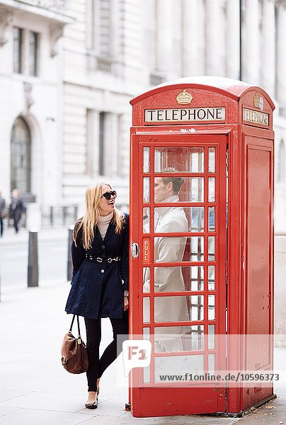 Young couple in red phone box  London  England  UK