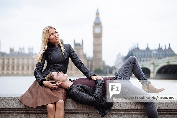 Young couple on wall in front of Big Ben  London  England  UK