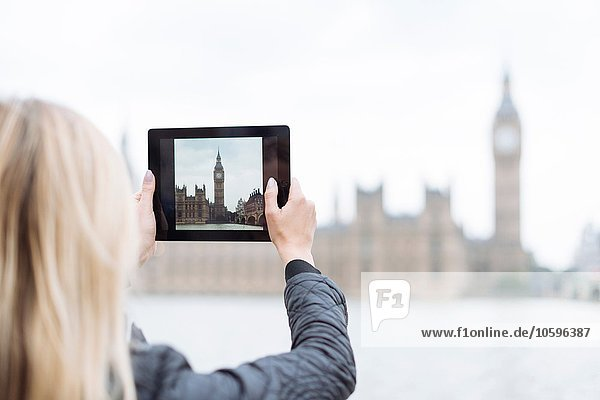 Rear view of young woman photographing Big Ben on digital tablet  London  England  UK