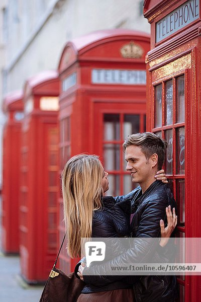 Romantisches junges Paar umarmt neben roten Telefonzellen  London  England  UK Romantisches junges Paar umarmt neben roten Telefonzellen, London, England, UK