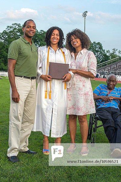 Teenagermädchen mit Eltern und Großvater bei der Abschlussfeier