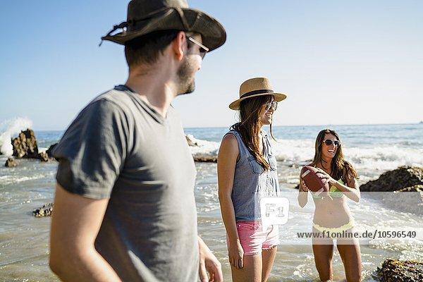 Drei erwachsene Freunde spielen American Football im Meer in Newport Beach  Kalifornien  USA