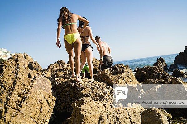 Rückansicht von jungen erwachsenen Freunden  die Felsen am Newport Beach  Kalifornien  USA  erkunden.