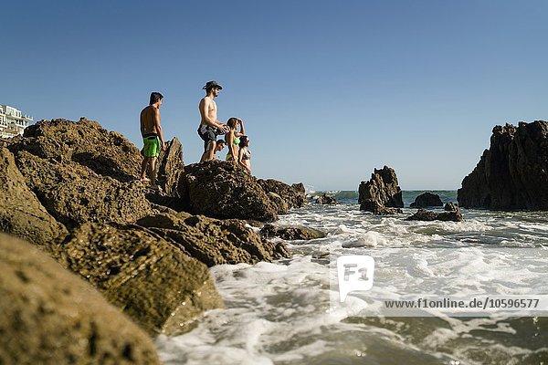 Junge erwachsene Freunde erkunden Felsen am Newport Beach  Kalifornien  USA