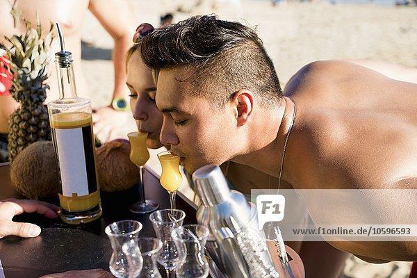 Junger Mann und Frau  die sich nach vorne lehnen  um einen Cocktail am Newport Beach  Kalifornien  USA zu trinken.