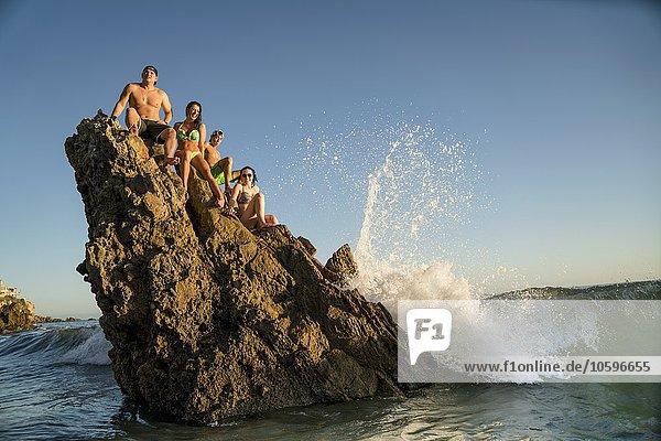 Erwachsene Freunde auf einer Felsformation in Newport Beach  Kalifornien  USA