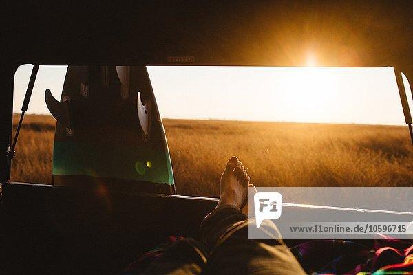 Männlicher Surfer mit nackten Füßen im Jeep bei Sonnenuntergang  San Luis Obispo  Kalifornien  USA