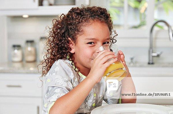 Mädchen an der Küchentheke trinkt Orangensaft mit Blick auf die Kamera