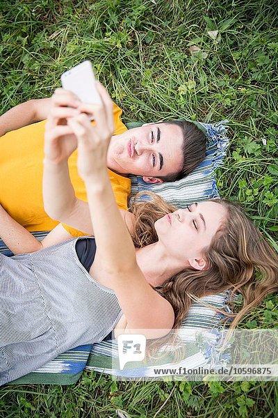 Junges Paar  das auf Gras auf dem Feld liegt und sich mit dem Smartphone selbst porträtiert. Junges Paar, das auf Gras auf dem Feld liegt und sich mit dem Smartphone selbst porträtiert.