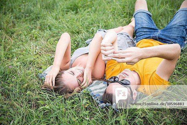 Junges Paar auf Rasen im Feld liegend  mit Blick auf Smartphone