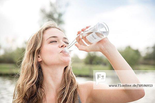 Junge Frau trinkt Wasser aus der Flasche  im Freien Junge Frau trinkt Wasser aus der Flasche, im Freien