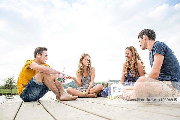 Gruppe junger Erwachsener am Steg sitzend  entspannend Gruppe junger Erwachsener am Steg sitzend, entspannend