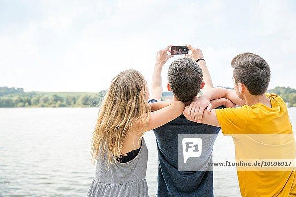 Drei junge Erwachsene beim Selbstporträt mit dem Smartphone  Rückansicht Drei junge Erwachsene beim Selbstporträt mit dem Smartphone, Rückansicht