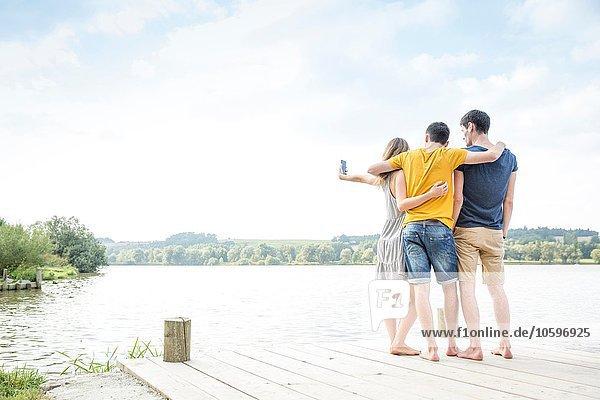 Drei junge Erwachsene am Steg stehend  Selbstporträt  mit Smartphone  Rückansicht