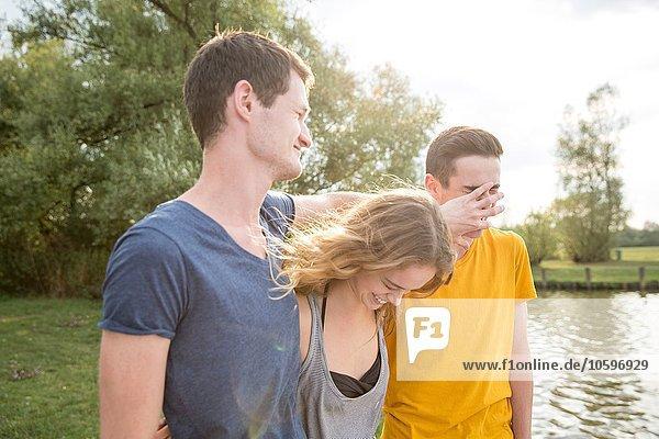 Gruppe junger Erwachsener  am See stehend  herumalbernd  lachend Gruppe junger Erwachsener, am See stehend, herumalbernd, lachend
