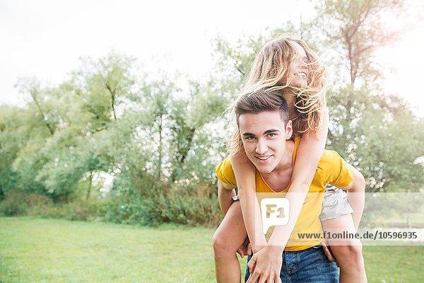 Junger Mann mit junger Frau auf dem Rücken  im Freien Junger Mann mit junger Frau auf dem Rücken, im Freien