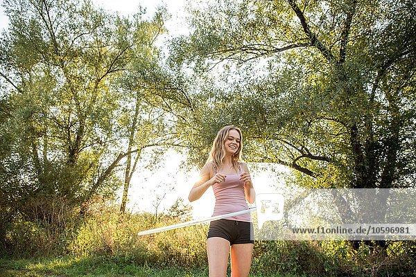 Junges Mädchen in ländlicher Umgebung  mit Hula Hoop  lächelnd Junges Mädchen in ländlicher Umgebung, mit Hula Hoop, lächelnd