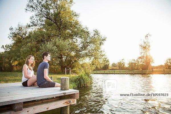 Junges Paar am Steg sitzend  entspannend Junges Paar am Steg sitzend, entspannend