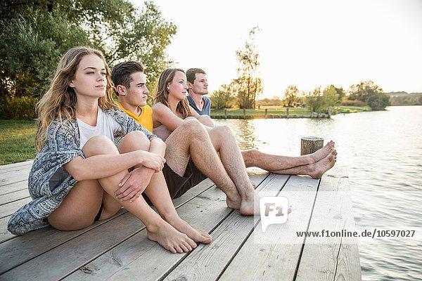 Gruppe von Freunden am Steg sitzend  entspannend