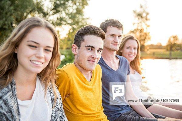 Porträt einer Gruppe von Freunden am See sitzend  lächelnd Porträt einer Gruppe von Freunden am See sitzend, lächelnd