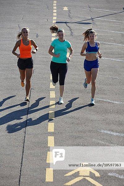 Drei junge Läuferinnen auf dem Parkplatz
