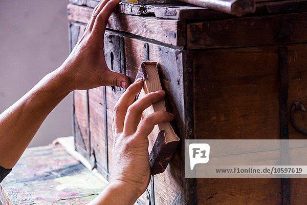 Manneshände schleifen Holzkoffer