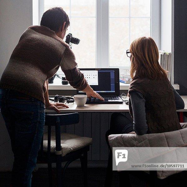 Mittlerer Erwachsener Mann und Frau mit Laptop am Schreibtisch  Rückansicht