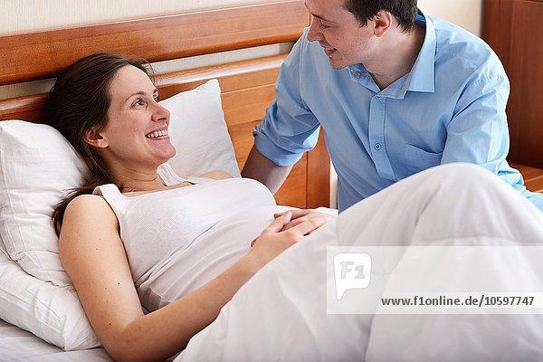 Schwangere Frau im Bett liegend  Mann neben ihr sitzend