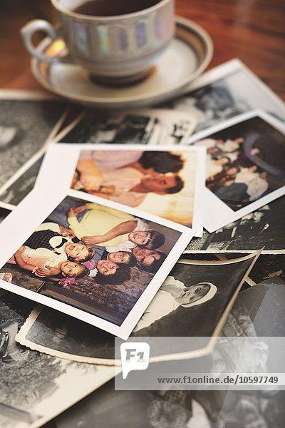 Stapel von Familienfotos auf dem Tisch,  neben der Teetasse