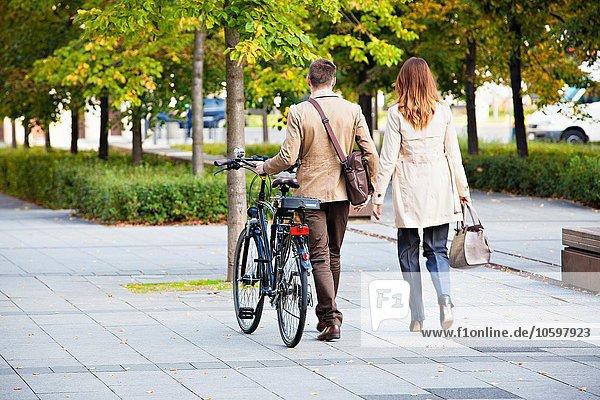 Gelegenheitskaufmann und -frau beim Fahrradfahren