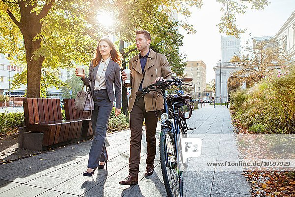 Lässiger Geschäftsmann und Frau  die das Fahrrad durch den Park schieben.