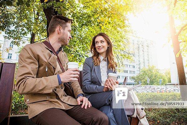 Lässiger Geschäftsmann und Frau im Park mit Kaffee