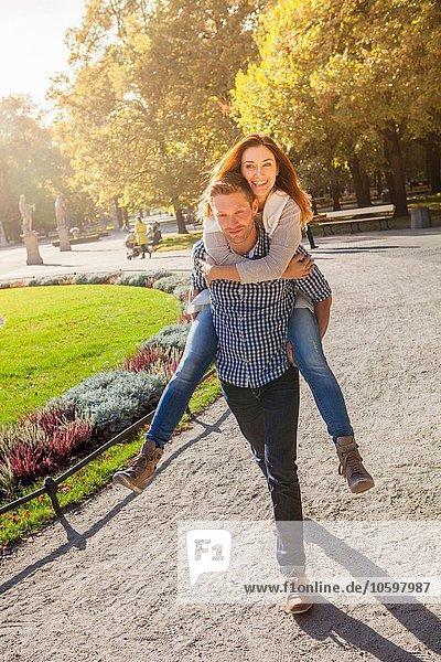 Mann schenkt Frau Huckepack im Park