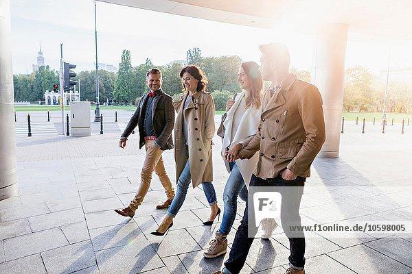 Vier erwachsene Freunde  die zusammen spazieren gehen.