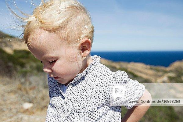 Female toddler looking down at coast  Calvi  Corsica  France
