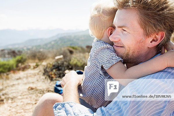 Mature man and toddler daughter hugging  Calvi  Corsica  France