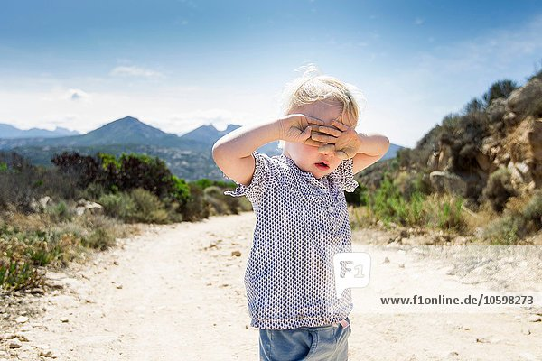 Female toddler on dirt track with hands covering eyes  Calvi  Corsica  France