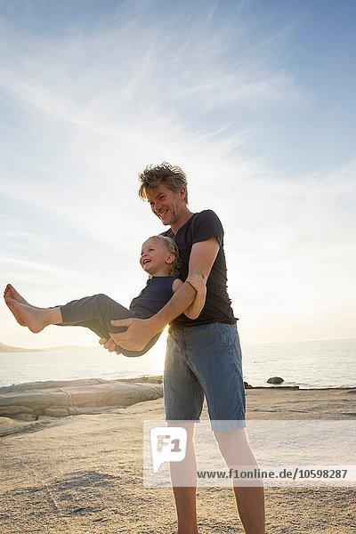 Mature man swinging his toddler daughter on beach  Calvi  Corsica  France