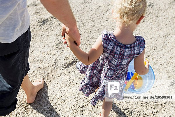 Father and female toddler strolling on beach with toy bucket