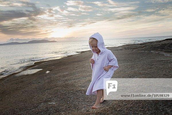 Female toddler wearing hooded robe on beach  Calvi  Corsica  France