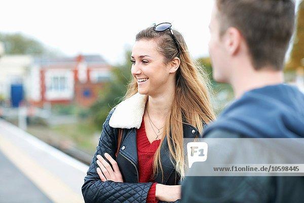 Junge Frau und junger Mann auf dem Bahnsteig stehend